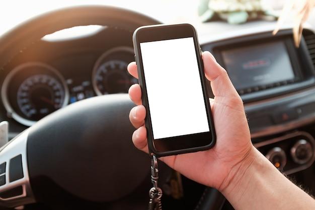 Hand, die telefon mit weißem schirm im auto hält