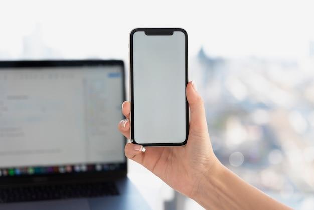 Hand, die telefon vor laptopmodell hält