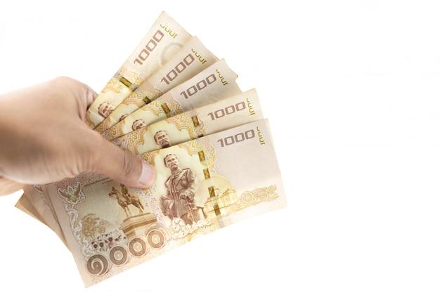 Hand, die thailändische banknoten fünftausend baht lokalisiert auf weißem hintergrund hält.