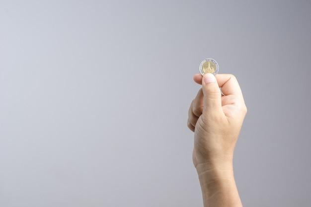 Hand, die thailändische münze oder währung hält