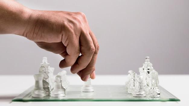 Hand, die transparente schachfiguren verschiebt