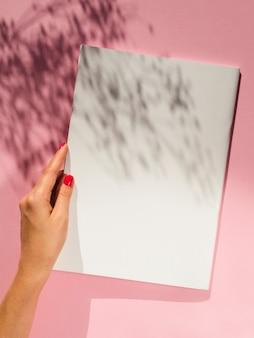 Hand, die unbelegtes papier mit schatten anhält