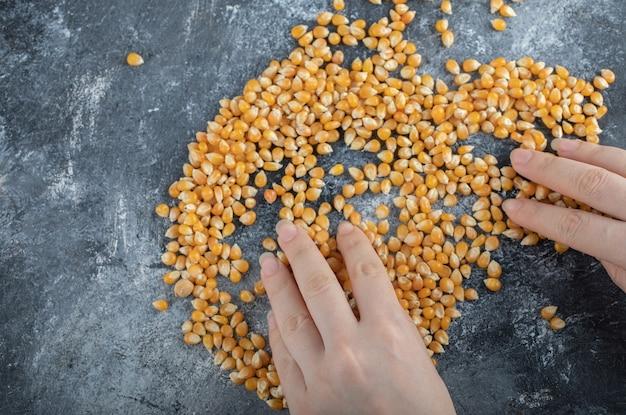 Hand, die ungekochte popcornsamen auf marmor verteilt.
