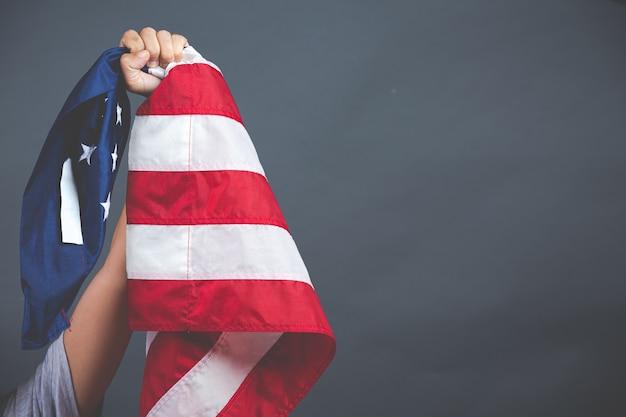 Hand, die usa-flagge auf dunklem hintergrund hält