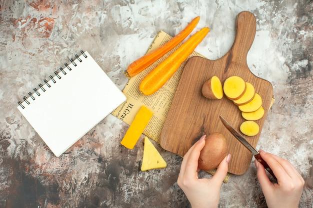 Hand, die verschiedenes gemüse und zwei arten käsemesser auf einem hölzernen schneidebrett auf einer alten zeitung hackt