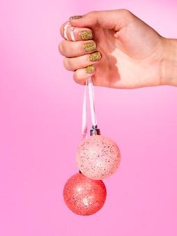 Hand, die verzierungsweihnachtsbälle hält