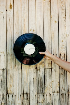 Hand, die vinylaufzeichnung über hölzernem hintergrund hält
