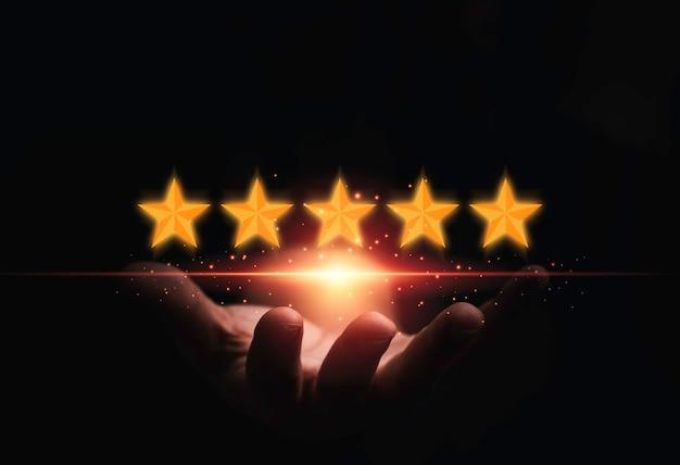 Hand, die virtuelle fünf goldene sterne mit leuchtendem licht hält, um die beste bewertung des kunden nach dem produkt- und servicekonzept zu erzielen.