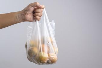 Hand, die voll Plastikbeutel von Orangen hält