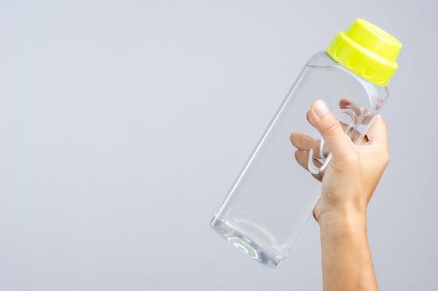 Hand, die volle 1,4 lites-wasserflasche hält