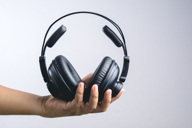 Hand, die vollen ohr- oder studiokopfhörer hält