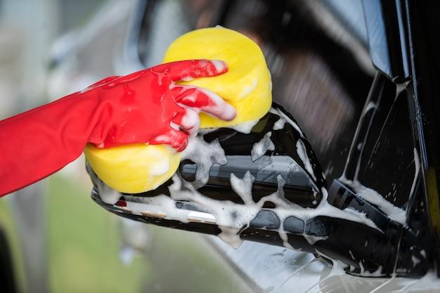 Hand, die waschende seitenspiegel des schwammes eines autos hält