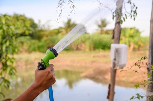 Hand, die wassersprüher mit bewässerung hält