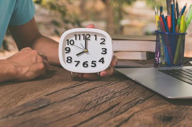 Hand, die wecker am schreibtisch hält.