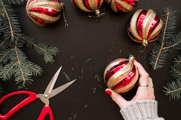 Hand, die weihnachtsflitter nahe den tannenzweigen hält