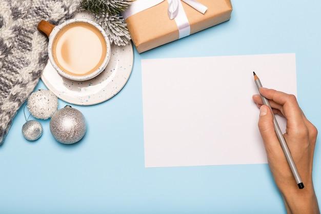 Hand, die weihnachtskarte, papiergeschenkbox und kaffee auf blauem hintergrund schreibt.