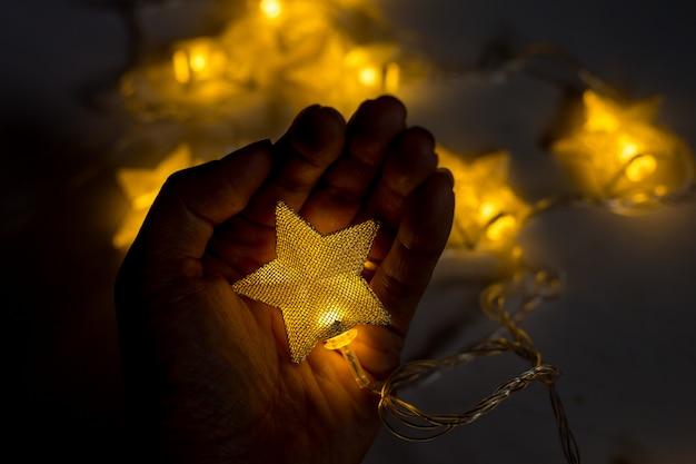 Hand, die weihnachtslampenstern auf weißem hintergrund hält