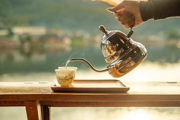 Hand, die weinlese-teekanne hält und heißen tee zur tasse auf holztisch gegen seeblick gießt