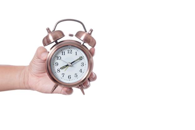 Hand, die weinleseweckereinstellung um 7am hält und zeit über acht uhr zeigt