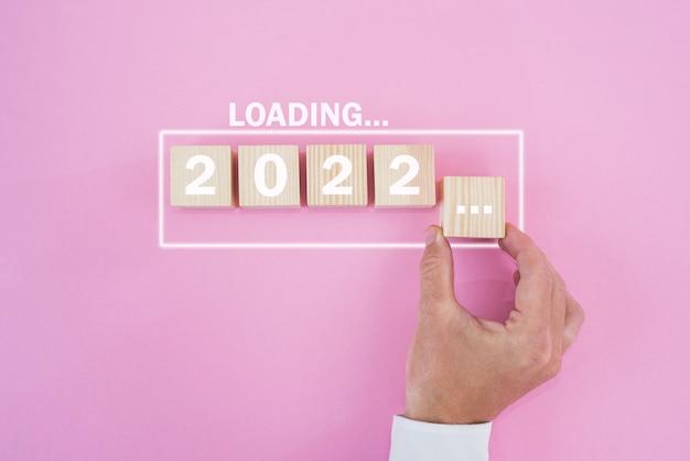 Hand, die weißen block zum laden des jahres 2021 bis 2022 setzt. start- und countdown-konzept.