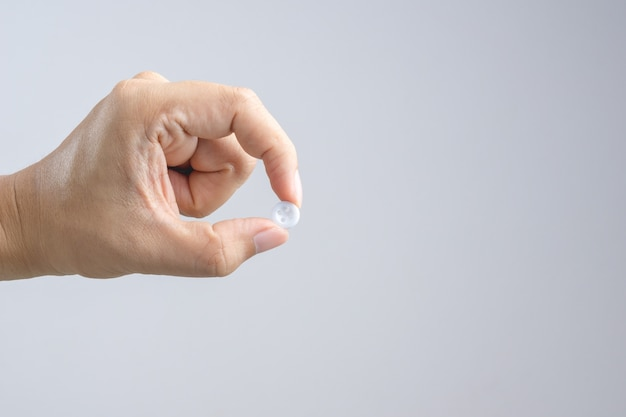 Hand, die weißen kleidungsknopf hält
