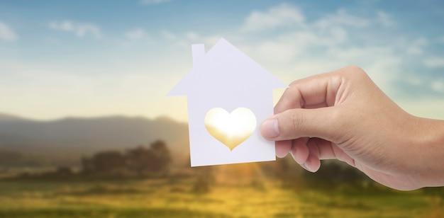 Hand, die weißes papierhaus mit herzförmigem fenster auf landschaftshintergrund hält
