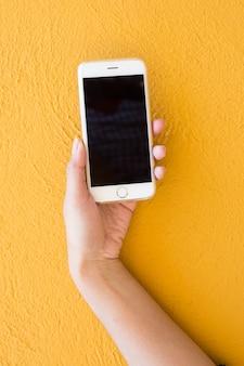 Hand, die weißes smartphone auf gelbem wandhintergrund hält