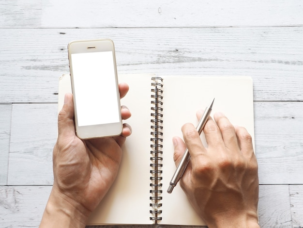 Hand, die weißes smartphone-display und stift auf leerem notizbuch auf weißer holztischplattenansicht hält