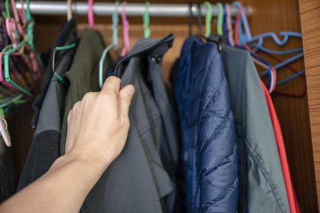 Hand, die winterjacke auf kleiderständer im holzschrank wählt