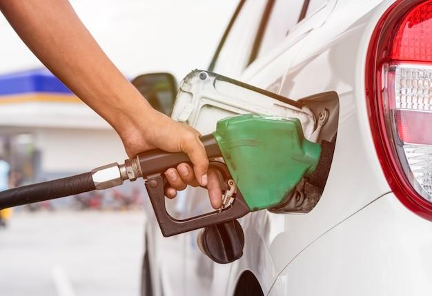 Hand, die zapfpistole hält, um benzin für auto an der tankstelle aufzutanken