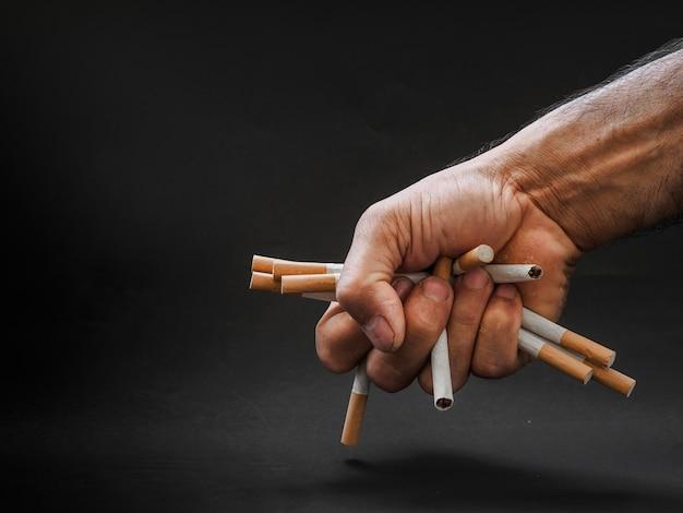 Hand, die zigaretten auf schwarzem hintergrund hält und zerstört. rauchendes konzept beenden.