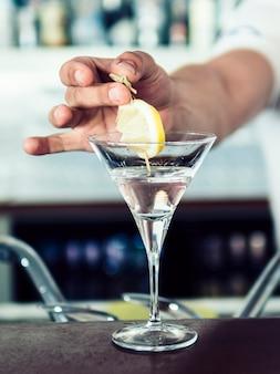 Hand, die zitrone im alkoholischen cocktail hinzufügt