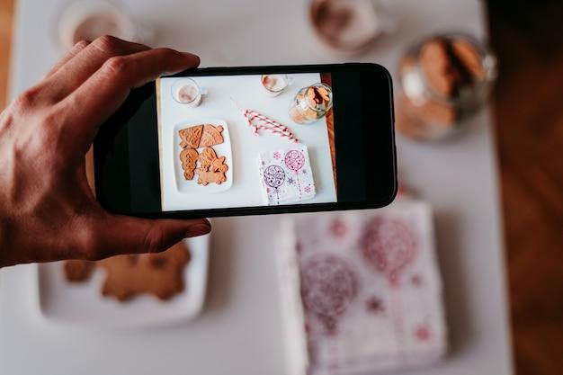 Hand, die zu hause ein foto mit handy von köstlichen weihnachtsbonbons macht