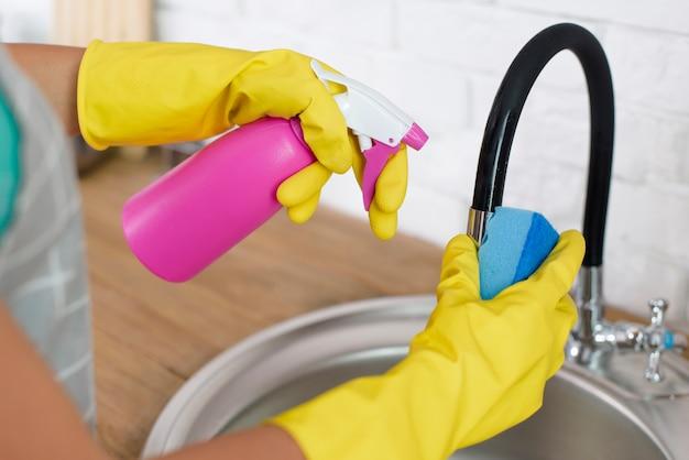 Hand, die zu hause sprühflasche und schwamm während der reinigungswanne hält