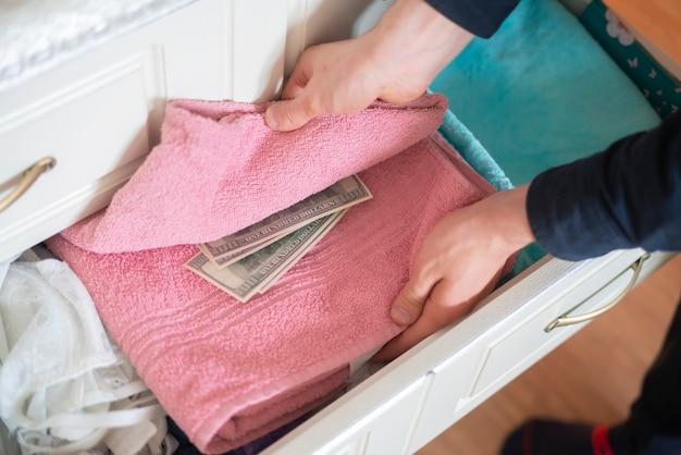 Hand, die zu hause versteckten vorrat an bargeld aus dem kleiderschrank nimmt