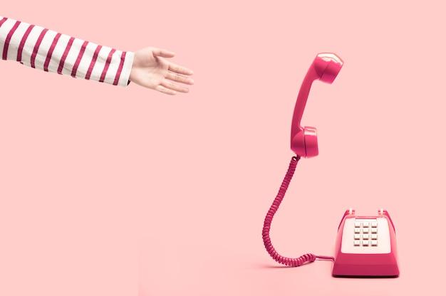 Hand, die zum rosafarbenen retro- telefon erreicht