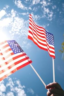 Hand, die zwei amerikanische flaggen auf dem blauen himmel mit sonnenlichthintergrund, winkende flagge für vereinigte staaten von amerika nahaufnahme hält
