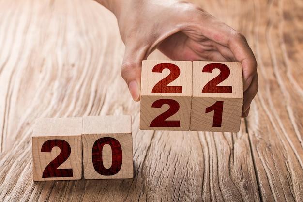 Hand dreht einen block um, der 2021 bis 2022 ändert. neujahr beginnt mit feiertagen und weihnachten