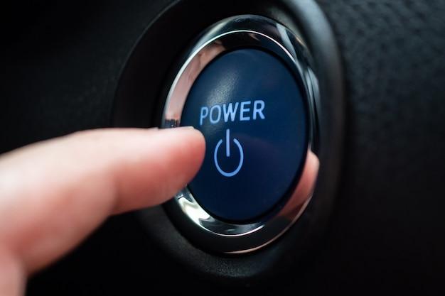 Hand drücken auf automotor-power-start-taste in der nähe