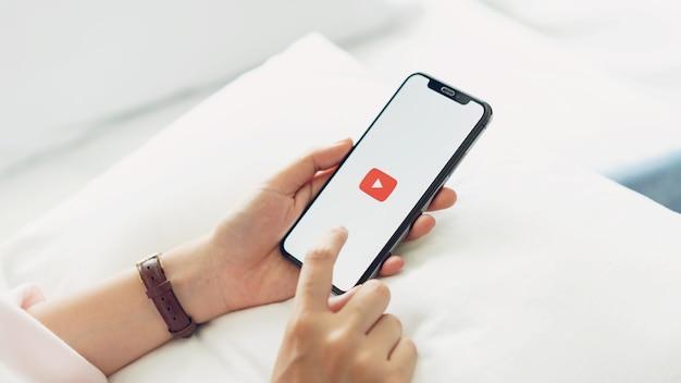 Hand drückt auf den bildschirm zeigt die youtube app icons auf apple iphone.