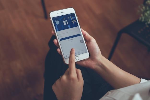 Hand drückt den facebook-bildschirm am telefon.