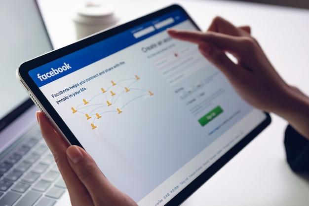 Hand drückt den facebook-bildschirm auf apple ipad pro, den social media für den informationsaustausch und das networking verwenden.