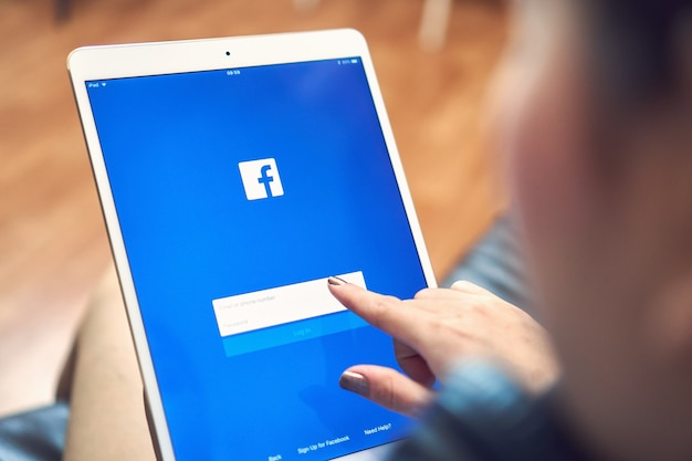Hand drückt den facebook-bildschirm auf den tisch