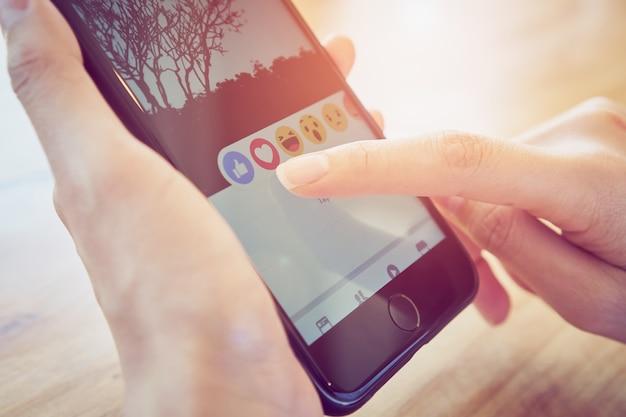 Hand drückt den facebook-bildschirm smartphone