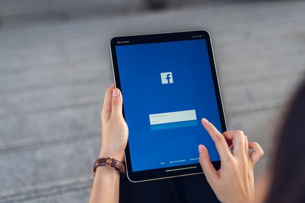 Hand drückt den facebook-bildschirm