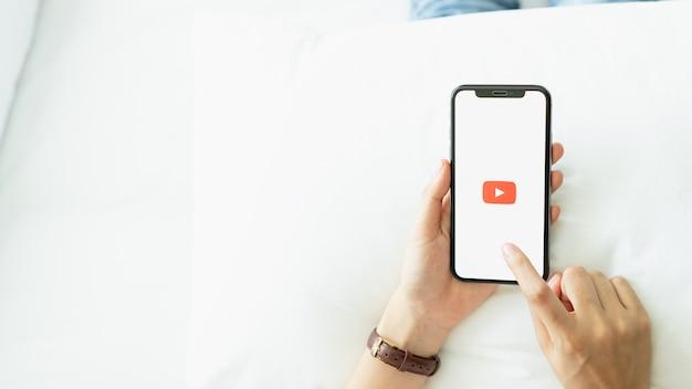Hand drückt der bildschirm und zeigt die youtube-app-symbole auf dem apple iphone an. youtube.