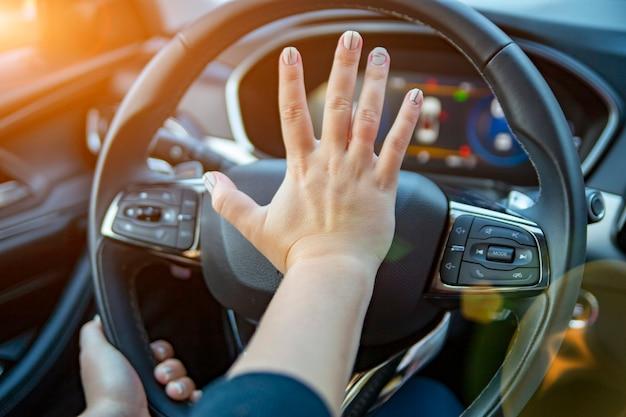 Hand drückt die hupe am lenkrad eines modernen autos ohne gesicht