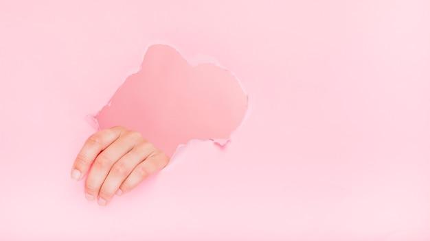 Hand durch ein papierloch