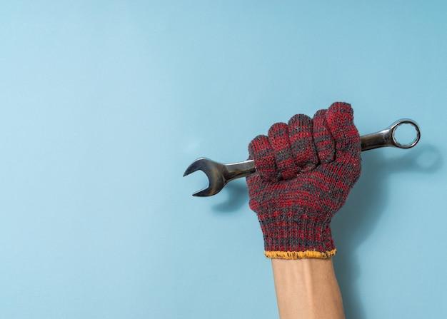 Hand einen mann halten schraubenschlüssel auf blauem hintergrund. konzept zum tag der arbeit. platz kopieren.