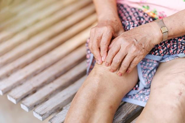 Hand einer älteren frau, die ein knie mit einer verletzung aufgrund von arthritis massiert